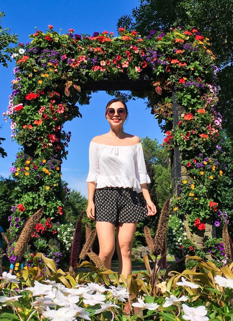 Montreal Botanical Garden floral arch Urban Planet off-the-shoulder top Forever 21 shorts sunglasses Asos sandals leather backpack (1)
