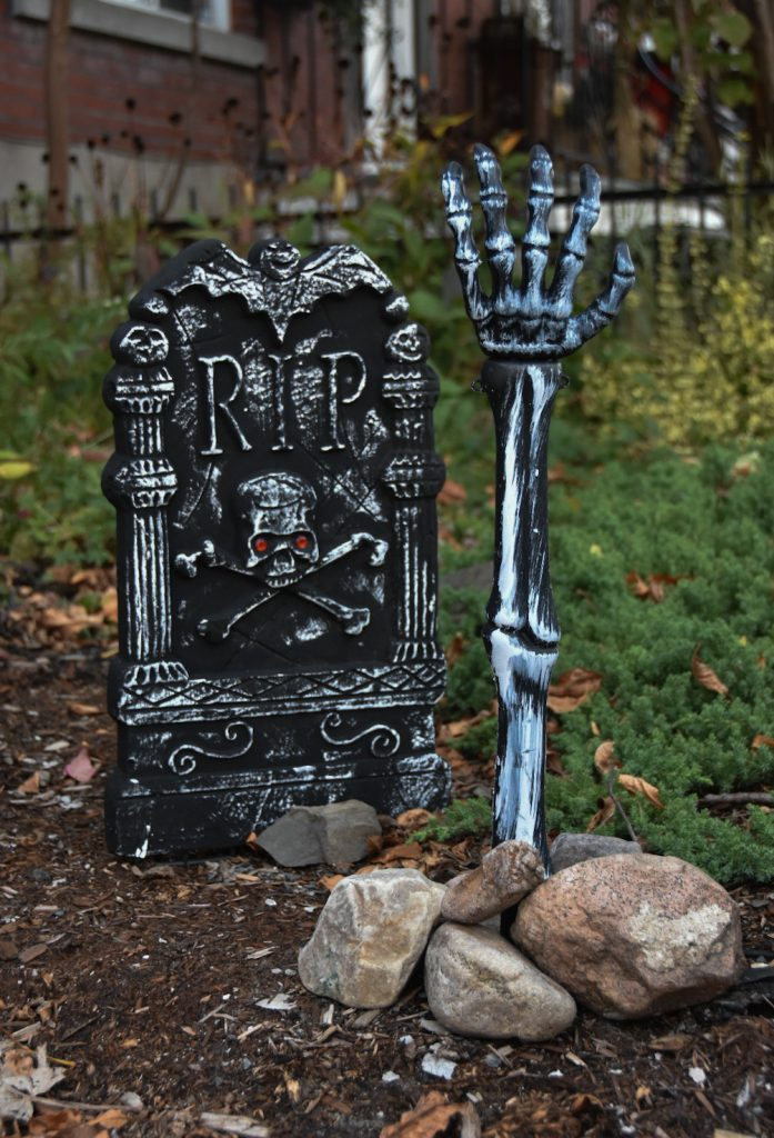 Halloween outdoor decor tombstone skeleton arm reaching out of the ground